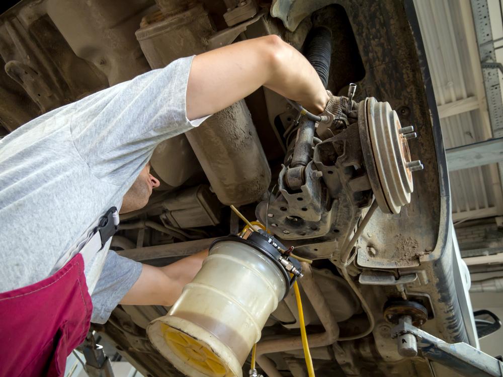 Ein Mechaniker entnimmt die alte Bremsflüssigkeit aus einem Auto, dass auf einer Hebebühne steht.