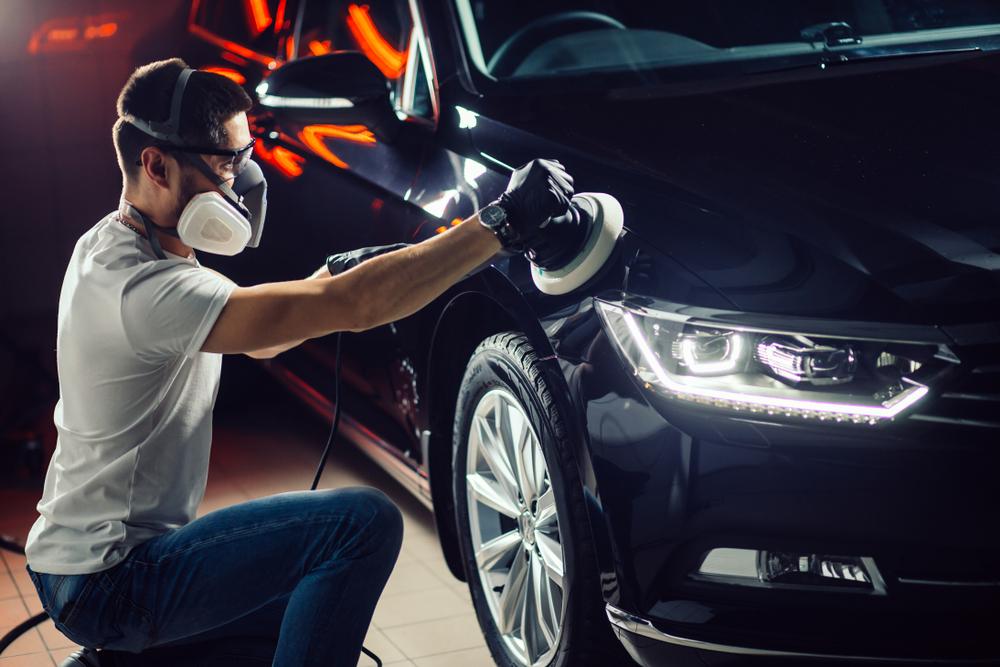 Ein junger Mann der Mundschutz und Handschuhe trägt poliert die rechte Seite der Motorhaube eines dunklen Autos. Dafür verwendet er eine Autopoliermaschine mit einem weichen Polierpad.