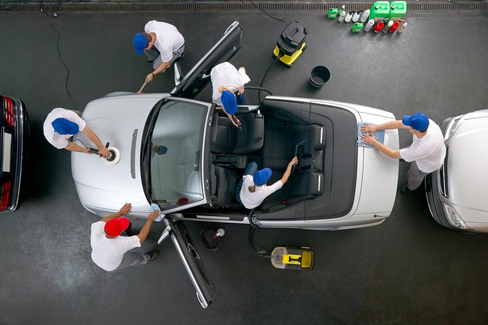 Ein siberner Cabrio wird zeitgleich von 6 Personen gereinigt.