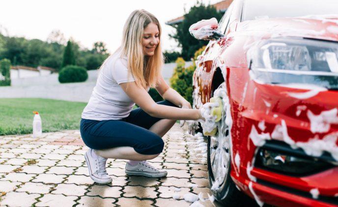 Eine junge Frau wäscht die Felgen eines roten Autos mit einem Schwamm.