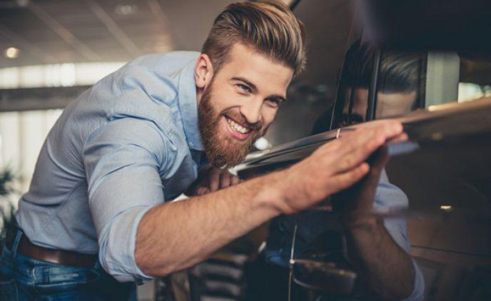 Ein junger Mann begutachtet freudig die sauberen Reflexionen in der Karosserie seines Autos und streicht dabei mit seiner Hand über den schwarzen Lack.
