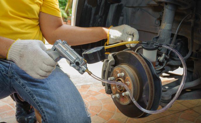 Mithilfe einer Pumpe wird hier eine PKW Bremse entlüftet.